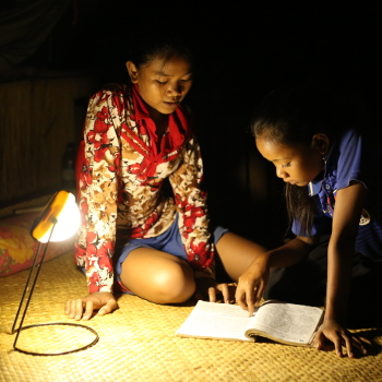 Des enfants travaillant éclairés avec une lampe distribuée par un programme énergie d'Entrepreneurs du Mondepe distribuée