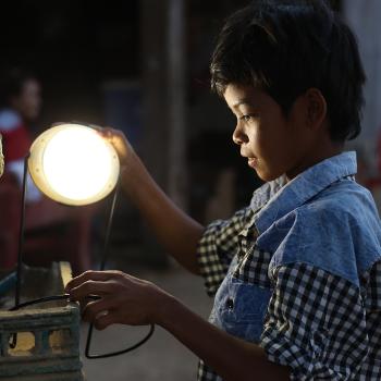 Un enfant découvrant une lampe distribuée par Entrepreneurs du Monde