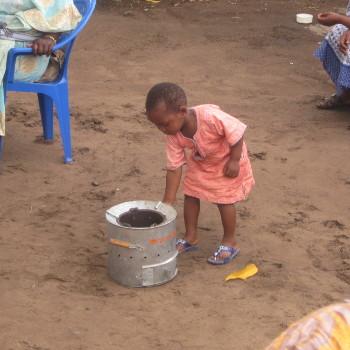 Une petite fille découvrant un réchaud distribué par Entrepreneurs du Monde