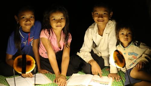 Enfants éclairés par une lampe solaire